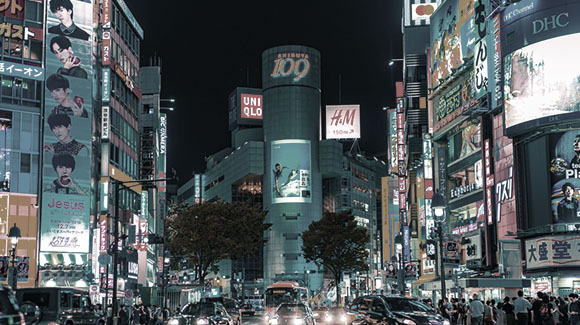 Japanese busy square with billboards and cars at night