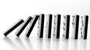 black and white dominoes aligned next to each other falling in a sequence